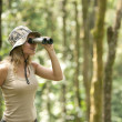 Young woman using binoculars in the rainforest. — ストック写真