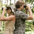 Stockfoto: Mand womback to back, looking through binoculars in forest.
