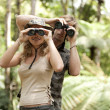 Man and woman in the forest looking at the camera through binoculars. — Stock Photo