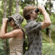 Man and woman back to back, looking through binoculars in the forest. — Stock Photo #21103365