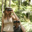 Stock Photo: Man and woman in the forest looking at the camera through binoculars.