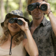 Man and a woman in the forest looking at the camera through binoculars. — Stock Photo