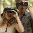 Man and a woman in the forest looking at the camera through binoculars. — Stock Photo #21103395