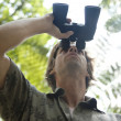 Underview of a man looking through binoculars in the forest. — Foto de Stock