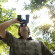 Photo: Underview of a man looking through binoculars in the forest.