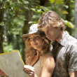 Couple reading a map in a tropical forest. — Stock Photo #21103451