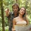 Couple reading a map in a tropical forest. — Stock Photo #21103481