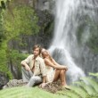 Couple sitting by tropical waterfalls. — Stock Photo
