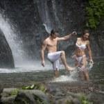coppia gettando acqua a vicenda sotto cascate — Foto Stock