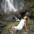 Young woman sitting down by waterfalls with her head back. - Stock Photo