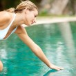 Attractive young woman kneeling by the edge of a swimming pool — Stok fotoğraf