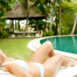 Foto Stock: Young womwearing bikini and lounging