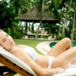 Young woman wearing a bikini and lounging in a tropical garden — Stock Photo