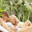 Young couple relaxing on a sun bed and kissing — 图库照片