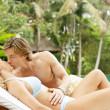 Young couple relaxing on a sun bed and kissing — Stockfoto