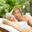 Young couple relaxing on a sun bed — Stockfoto