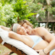 Young couple hugging on a sun bed in a villa's tropical garden while on vacation. — Стоковая фотография