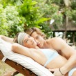 Young couple hugging on a sun bed in a villa's tropical garden while on vacation. — Стоковое фото