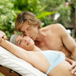 Young couple relaxing on a sun bed and kissing in a villa's tropical garden — Stok fotoğraf