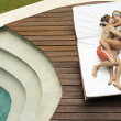 Young couple playfully hugging and kissing on a sun lounger by the swimming pool. — Stock Photo