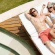 Attractive couple sunbathing by a swimming pool while on holiday. — Стоковое фото