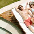 Attractive couple sunbathing by a swimming pool while on holiday. — Stock Photo #21103885