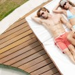 Attractive couple sunbathing by a swimming pool while on holiday. — Stockfoto
