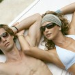 Royalty-Free Stock Photo: Young attractive couple sunbathing and wearing sunglasses.