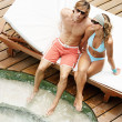Attractive couple sunbathing and sharing a sun bed by a swimming pool. - Stock Photo