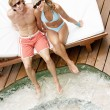 Attractive couple sunbathing and being affectionate while sitting by a swimming pool's  — Stock Photo
