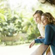 Young couple on vacations, leaning on a balcony's veranda - Stock Photo