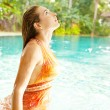 Sexy young woman emerging in a swimming pool - Stock Photo