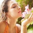 Young attractive girl smelling a tropical pink flower — Stock Photo #21104401
