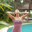 Sexy woman under tropical rain in an exotic garden with a swimming pool. — Stock Photo