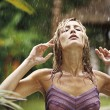 Attractive young woman under the tropical rain — Stock Photo
