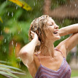 Portrait of a beautiful woman enjoying tropical rain falling on her in an exotic garden. — Stock Photo