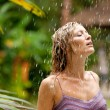 Stock Photo: Attractive woman under tropical rain in an exotic garden.