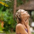 Attractive woman under tropical rain in an exotic garden. — Photo