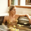 Young attractive woman bathing with flowers and petals in a health spa's bath. - Stock Photo