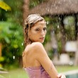 Portrait of a beautiful happy woman enjoying tropical rain falling on her in an exotic garden. — Stock Photo