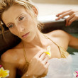 Attractive woman in a bath of flowers — Stock Photo #21104805