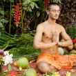 Young man in a yoga position in an exotic garden. — Stock Photo #21104887