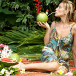 Young attractive woman surrounded by tropical fruits in an exotic garden. — Stock Photo