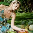 Young attractive woman surrounded by tropical fruits in an exotic garden. — Stock Photo #21104909