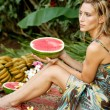 Young attractive woman surrounded by tropical fruits in an exotic garden. — Stockfoto