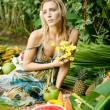 Young attractive woman surrounded by tropical fruits in an exotic garden. — Stock Photo #21104927