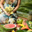 Young woman surrounded by tropical fruits in an exotic garden. — Foto de Stock