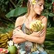 Young attractive woman surrounded by tropical fruits in an exotic garden. — ストック写真