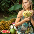 Young attractive woman surrounded by tropical fruits in an exotic garden. — Stock Photo #21104949