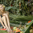 Stock Photo: Young woman in a tropical forest sitting on a bed of fruits and flowers.